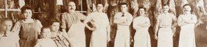 Historisches Bild einer Metzgerei mit Mitarbeitern und Familie des Inhabers.