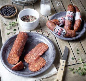 Holztisch für Brotzeit mit PICK Paprika-Kobasz geschnitten auf einem Teller angerichtet mit Pfefferkörnern und Salz.