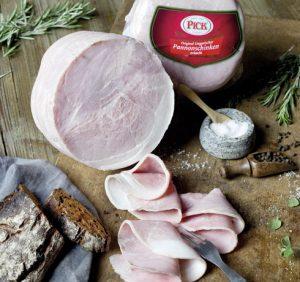 PICK Pannonschinken in Scheiben geschnitten und auf einem Holzbrett mit Brot, Salz und Pfeffer schön angerichtet.