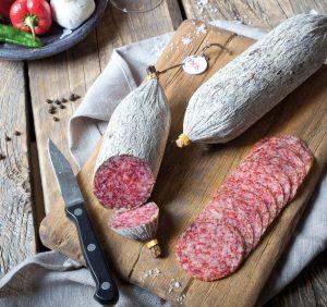 PICK original ungarische Salami angeschnitten auf Holzbrett mit Paprika und besten Salamizutaten